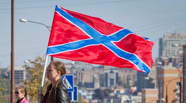 Eine Frau geht mit einer Flagge der Neurussland während einer Kundgebung am Lenin-Platz im Zentrum von Donezk, Osten der Ukraine. © Shamil Zhumatov / Reuters