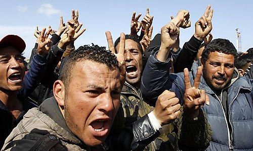 People fleeing the unrest in Tunisia protest against conditions on the southern Italian island of Lampedusa March 25, 2011. Italy will help Tunisia fight illegal migration to try to stem the flow of thousands of migrants following unrest in North Africa, Foreign Minister Franco Frattini said on Friday. Residents of Lampedusa, a sleepy port which lives off fishing and tourism, have complained of being abandoned by the government in Rome as a reception centre on the island has been filled to overflowing. REUTERS/Alessandro Bianchi (ITALY - Tags: POLITICS CIVIL UNREST SOCIETY)